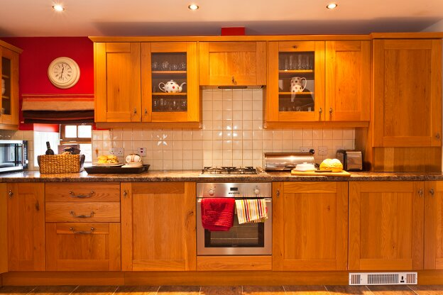 The large oak kitchen contains a fan oven, gas hob, microwave oven, dishwasher, washer dryer, and a fridge with freezer compartment.